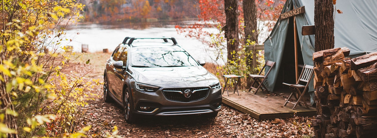 Image of the 2018 Buick TourX parked in a wooded area in front a tent.