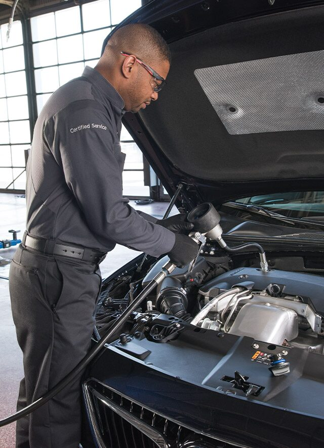 Buick Certified Service Technician Works Under the Hood of Vehicle