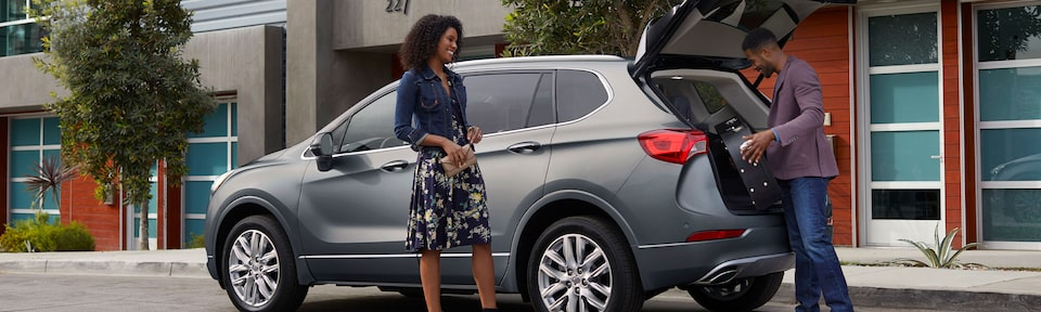 A couple unloads their luggage from the trunk of their Buick Envision SUV