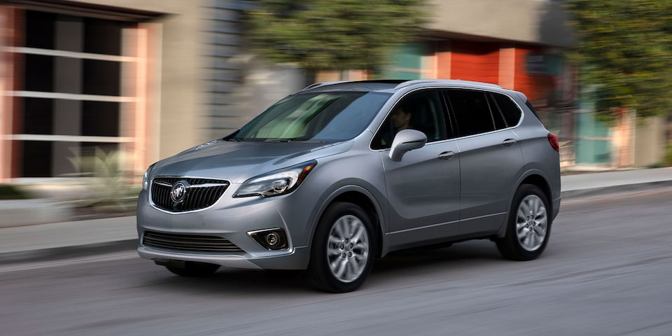Buick Envision SUV drives on a city road