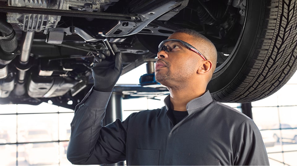 Buick Certified Service technician inspecting the underside of a vehicle