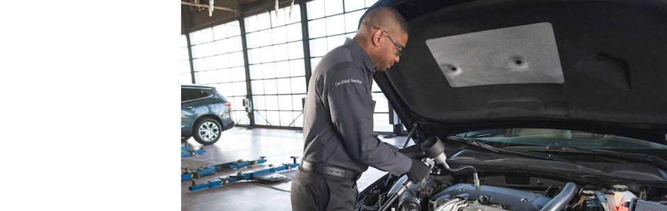Buick Certified Service technician working under the hood of a vehicle