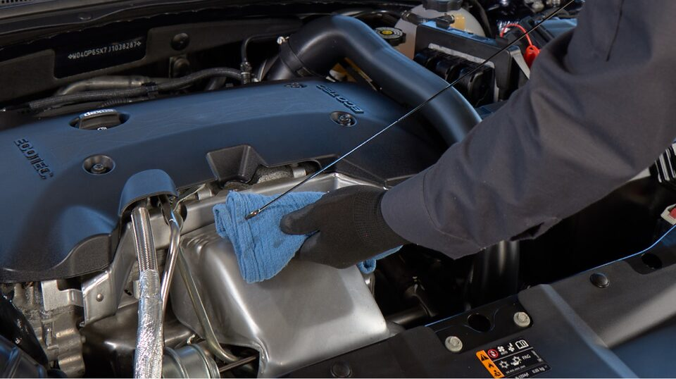 Buick Certified Service technician checking the oil of a vehicle