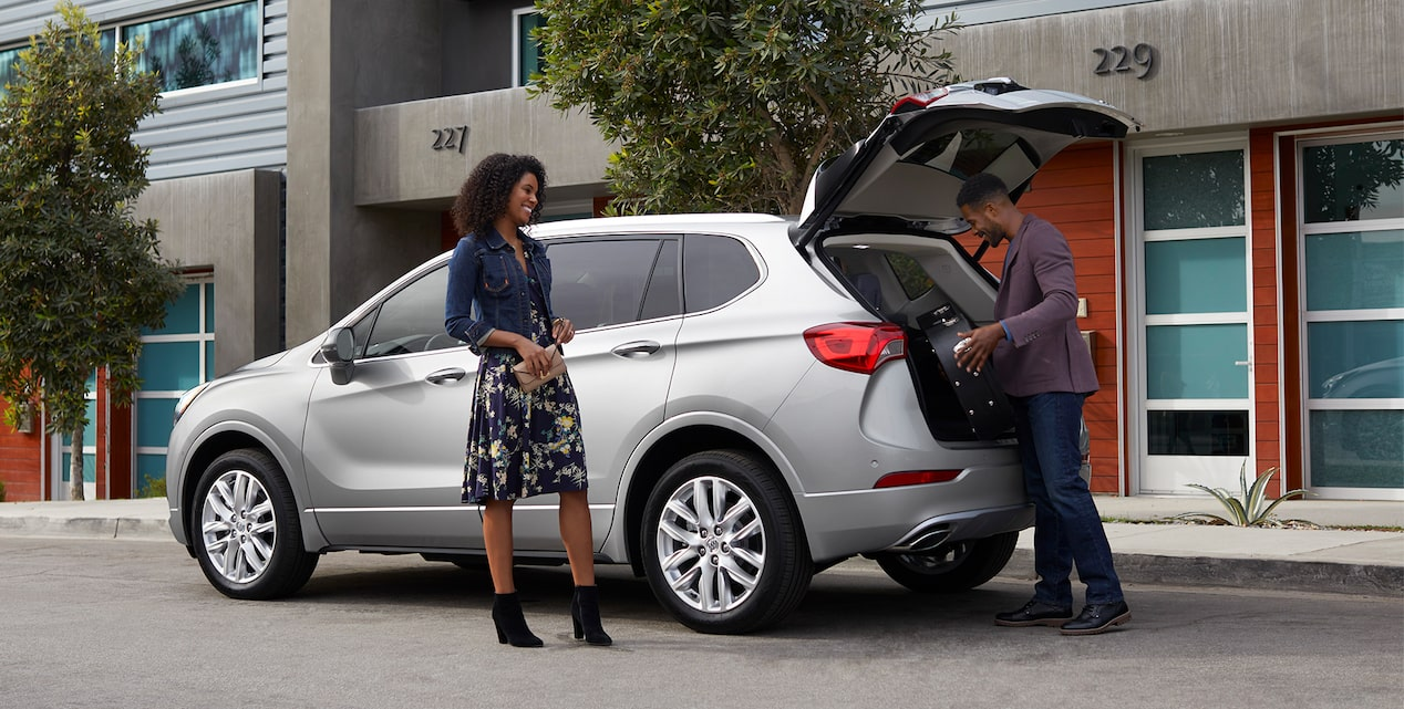 Image of a man loading a package into the cargo area of a Buick vehicle while a woman looks on.