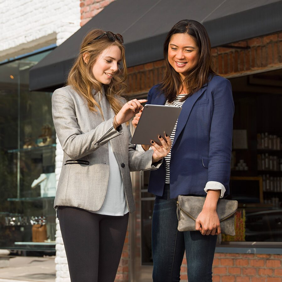 Image of two women using a tablet to access Buick Connected Services.