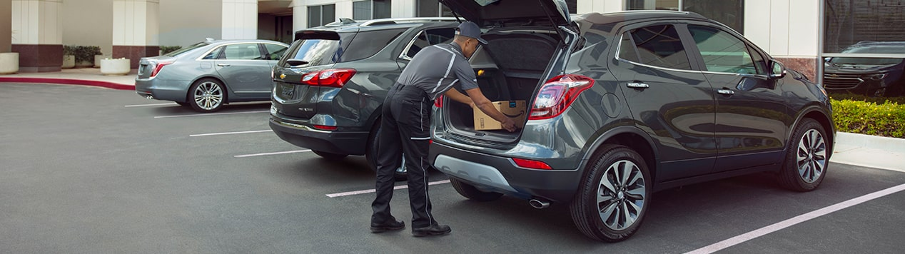 Image of a man loading a package into the cargo area of a Buick vehicle.
