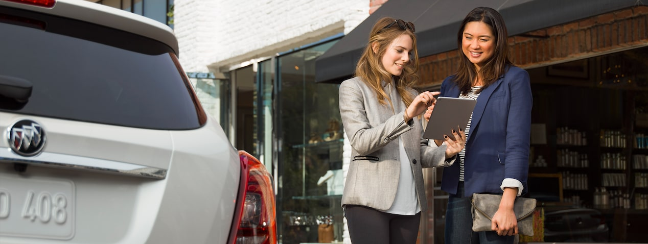 Image of two women using a tablet with connected services for a Buick vehicle.