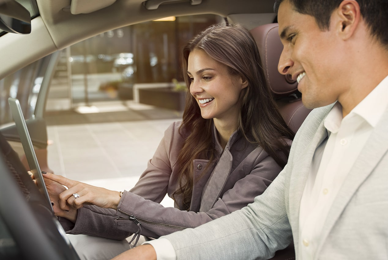 Image showing a man and a woman enjoying the hand free calling feature in a Buick vehicle.