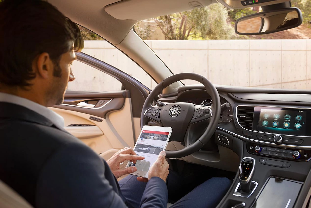 Image of a man using a tablet to access the convenient in-car Wi-Fi hotspot in his Buick vehicle.