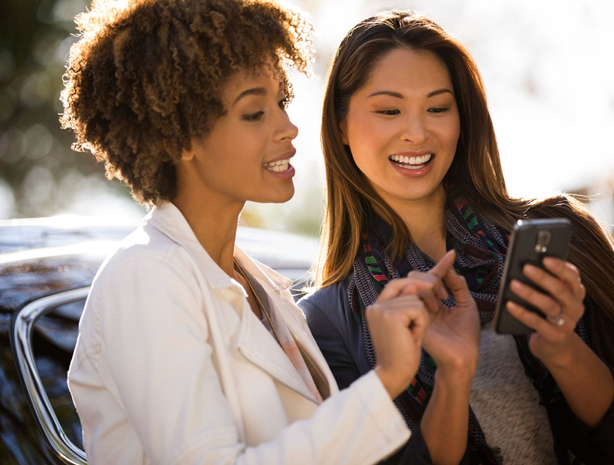 Image of two women looking at a smartphone screen.