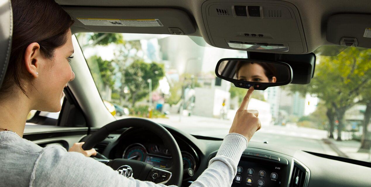 Image of a woman using the OnStar services of her Buick vehicle.