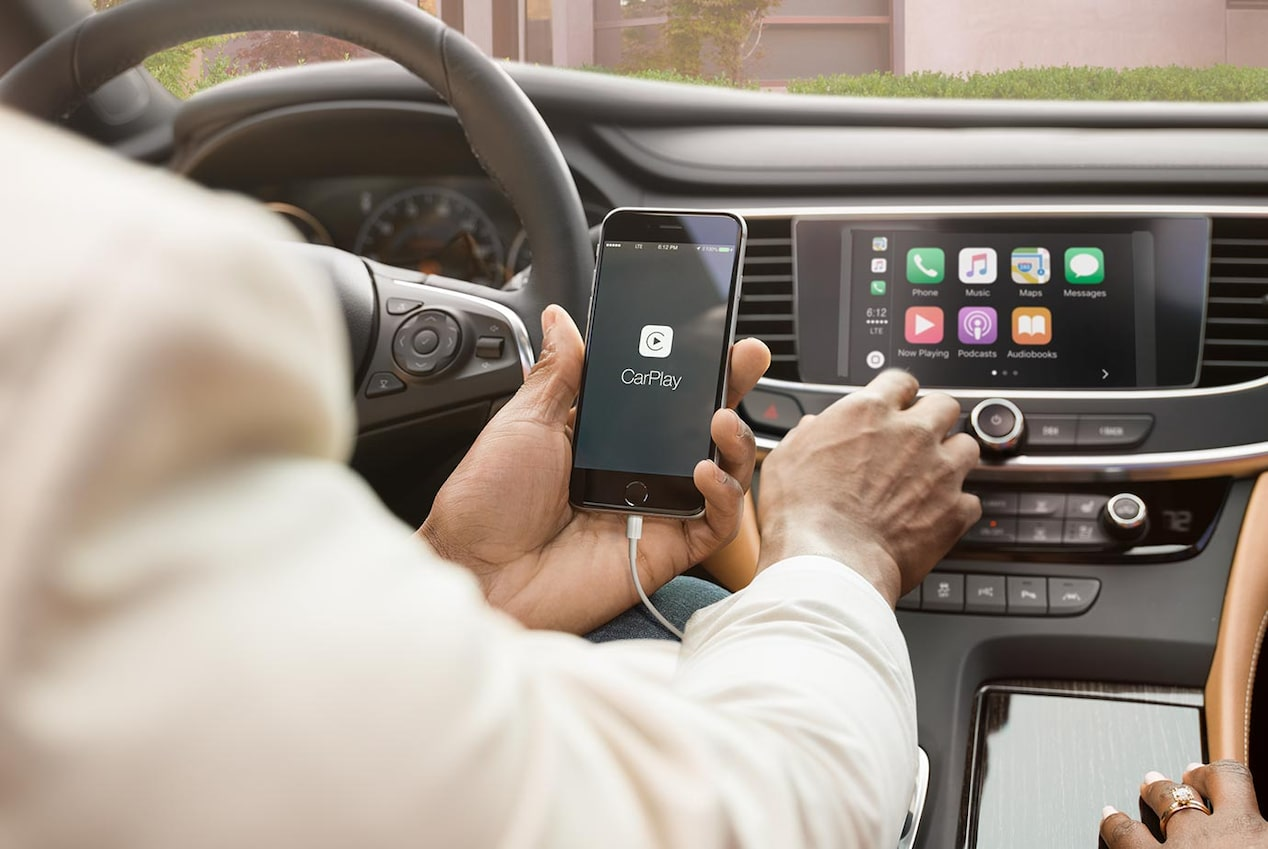 Image of someone using their iPhone to connect to the Apple CarPlay pairing features in a Buick vehicle.