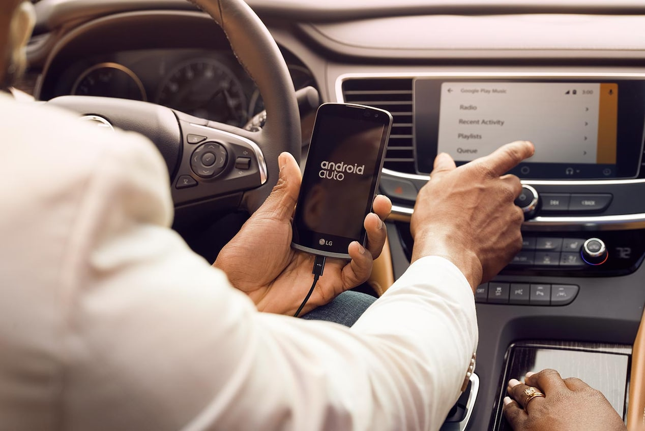 Image of someone using their smartphone to connect to the Android Auto pairing  features in a Buick vehicle.