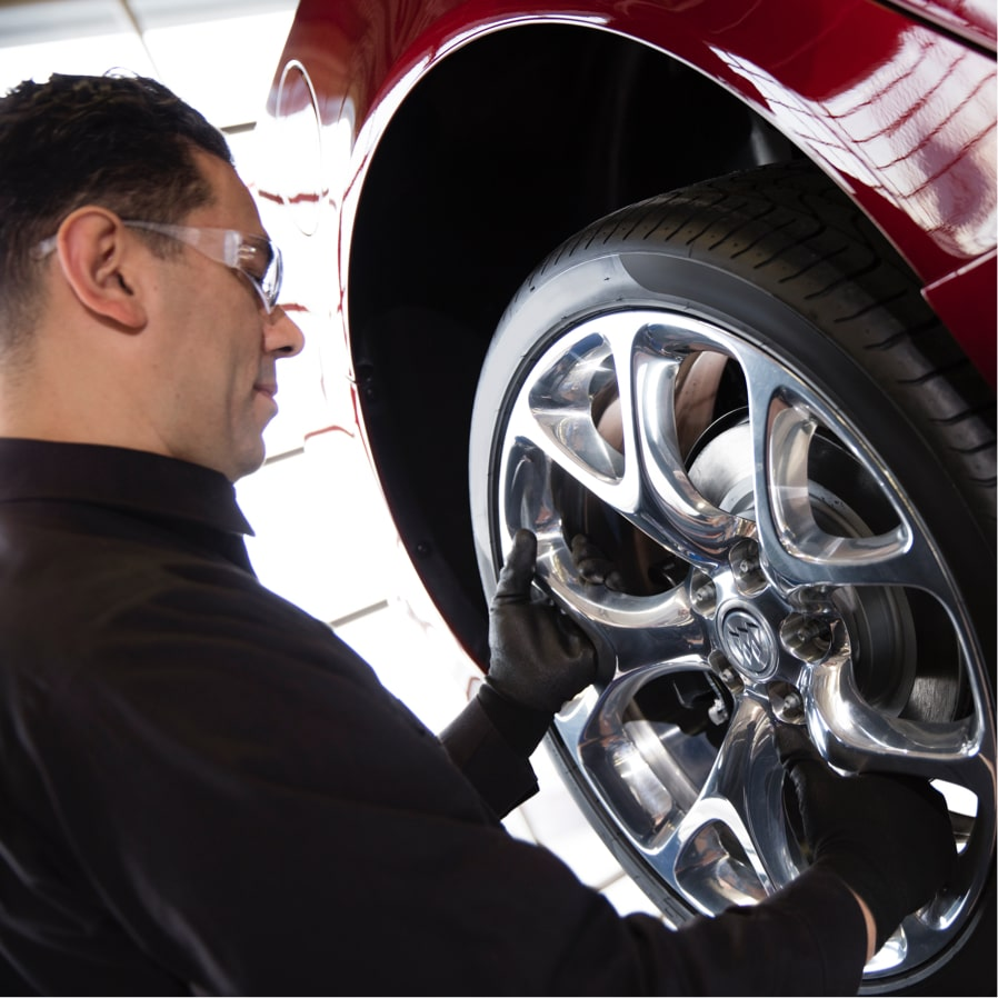 Image of a man changing a tire on a Buick vehicle.
