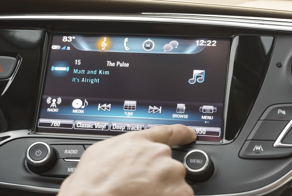 Image of a person using the color touch radio in a Buick vehicle.