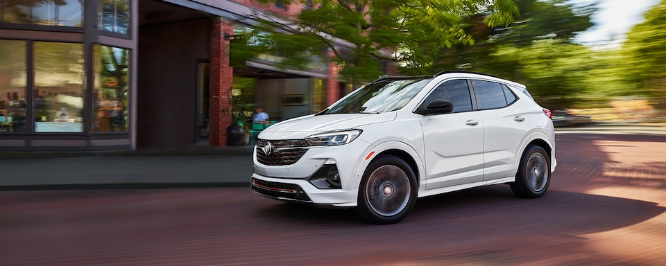 White Buick Encore GX Small SUV driving city streets