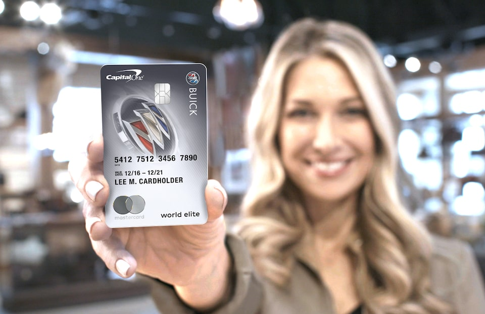 Image of woman holding the Buick BuyPower card from CapitalOne in the foreground.