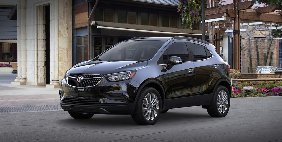 2019 Buick Encore Small Luxury SUV:  Exterior quarter view in front of storefronts. Proud partner of the NCAA.