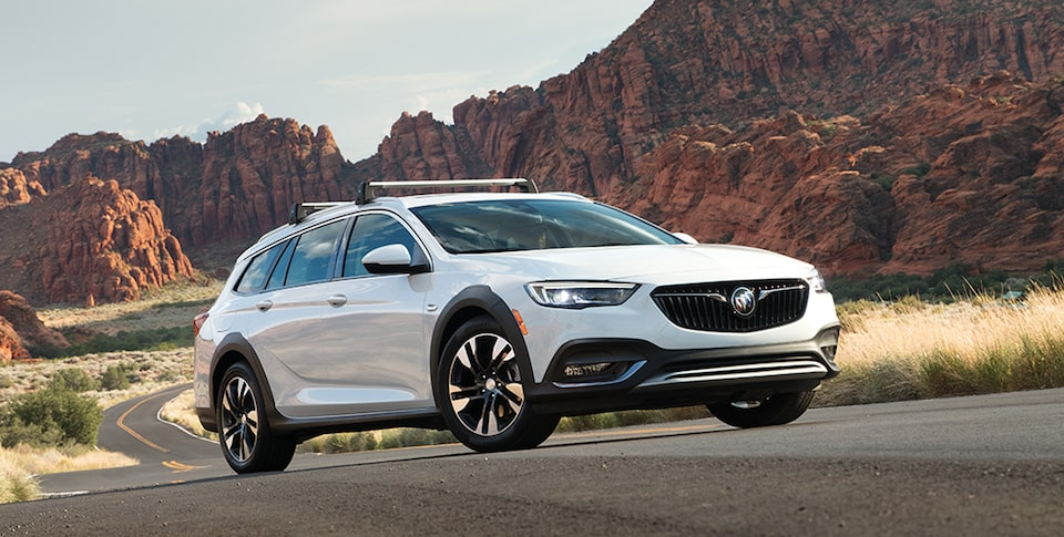 2019 Buick Regal Tourx Luxury Wagon: Exterior quarter shot with scenic mountain view. Proud partner of the NCAA.
