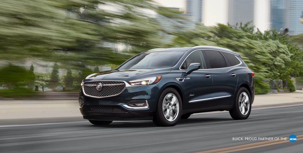 2019 Buick Enclave Mid-Size Luxury SUV: Driving in front of a city action shot. Proud partner of the NCAA.