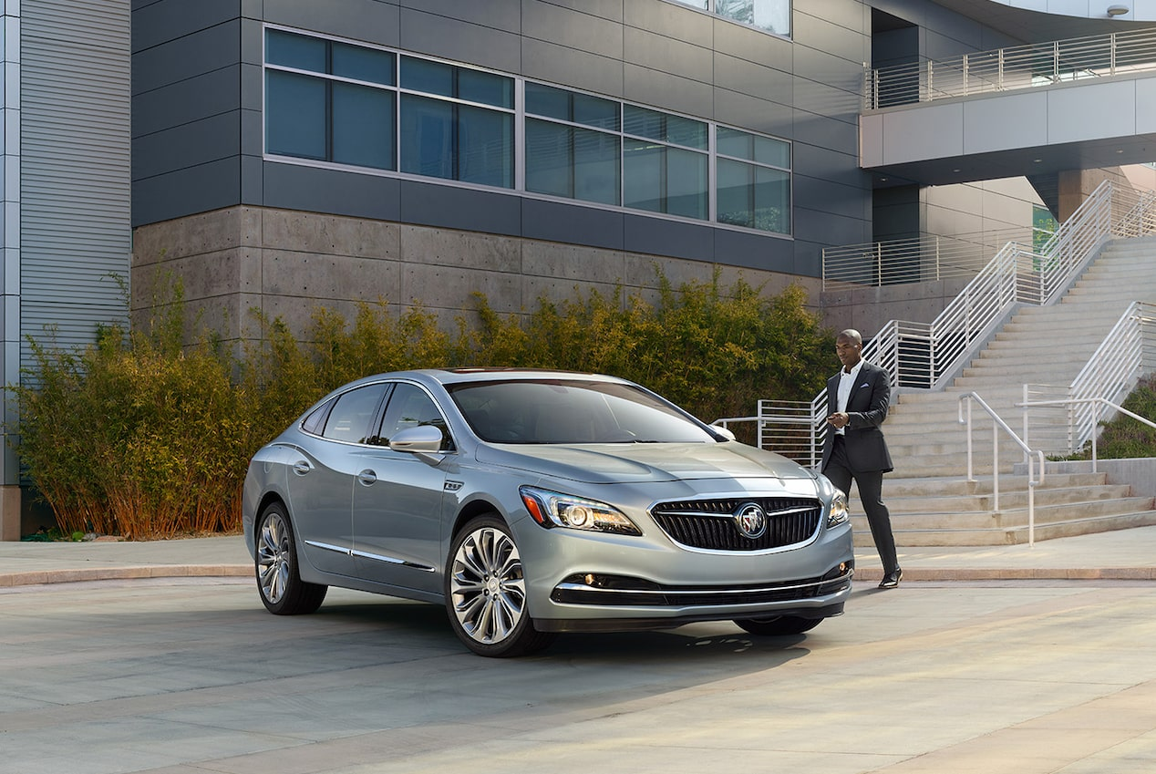 Image of a man in a suit approaching the 2017 Buick LaCrosse full-size luxury sedan parked in front of an office building.
