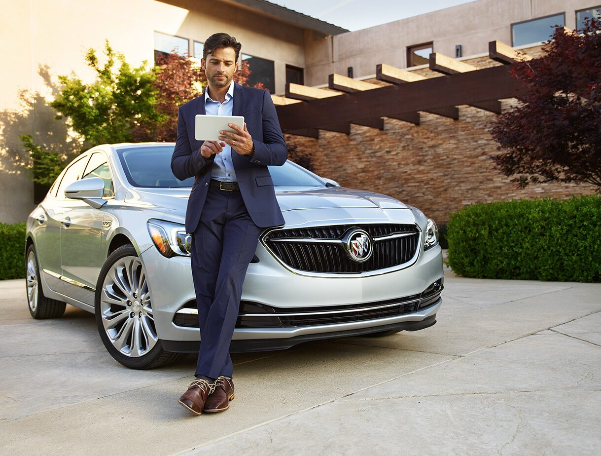 Image of a man in a suit leaning on the hood of the 2017 Buick LaCrosse full-size luxury sedan using a tablet.