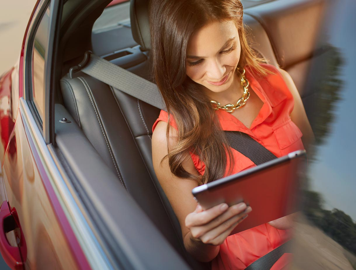Image of a woman using a tablet to access the available 4G LTE Wi-Fi Hotspot in the 2017 Buick Regal mid-size luxury sedan.