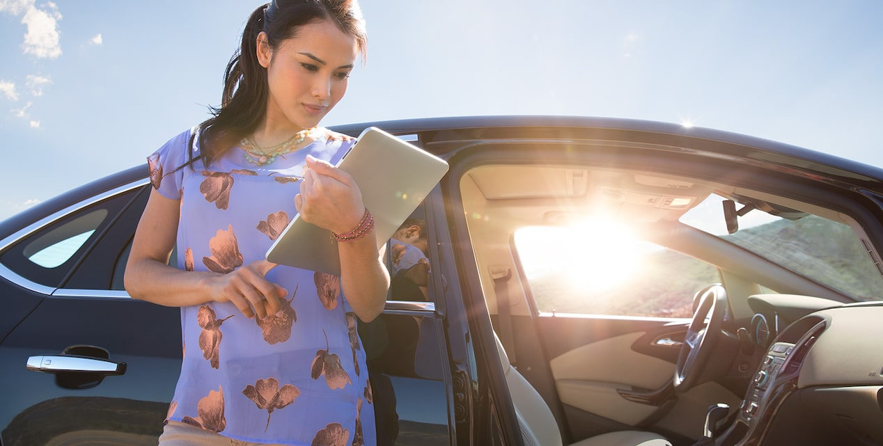 Image of a woman using a tablet to access the OnStar 4G LTE Wi-Fi hotspot in the 2017 Buick Verano small luxury sedan.