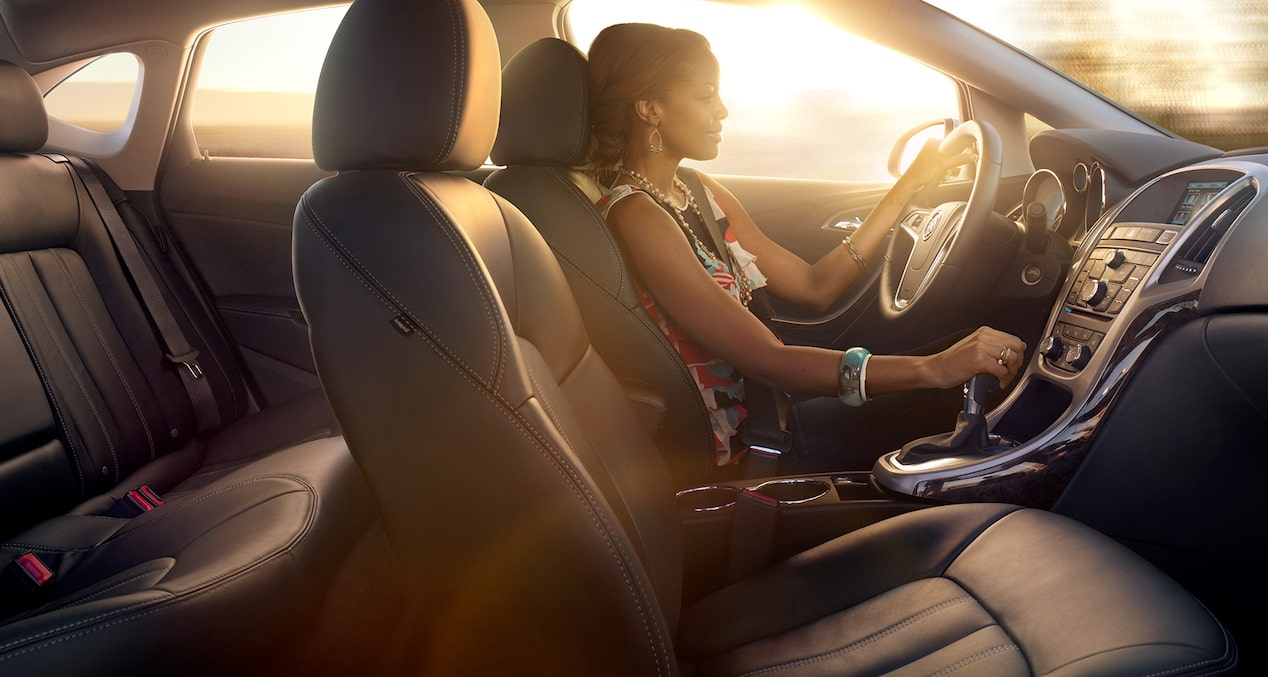Image of a woman driving in the 2017 Buick Verano small luxury sedan.