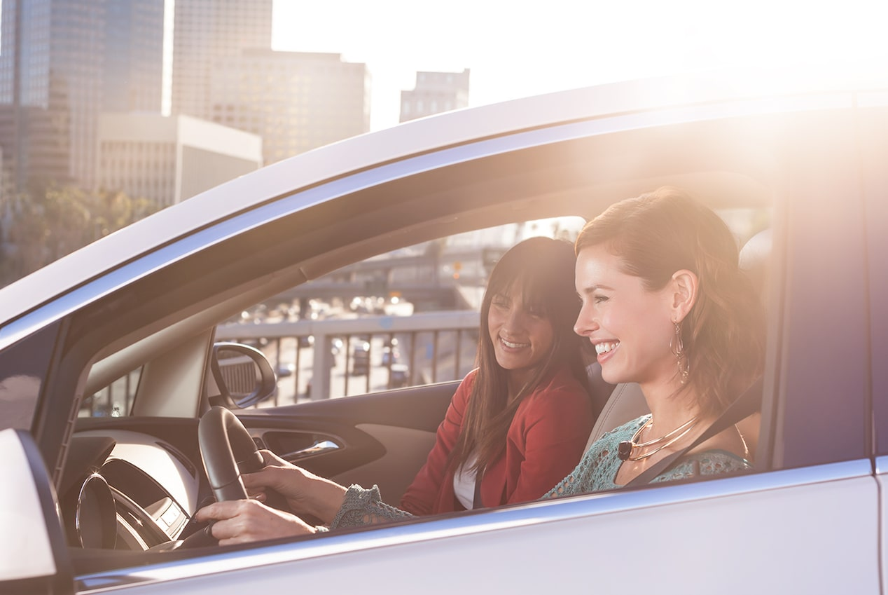 Image of the two women enjoying themselves in the driver and passengers seat in the 2017 Buick Verano small luxury sedan.