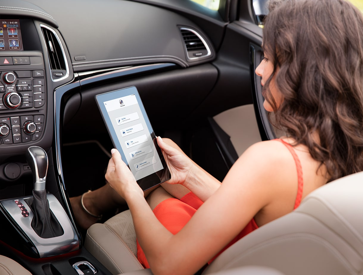 Image of a woman using the available 4G LTE Wi-Fi hotspot on her tablet in the 2017 Buick Cascada luxury convertible.
