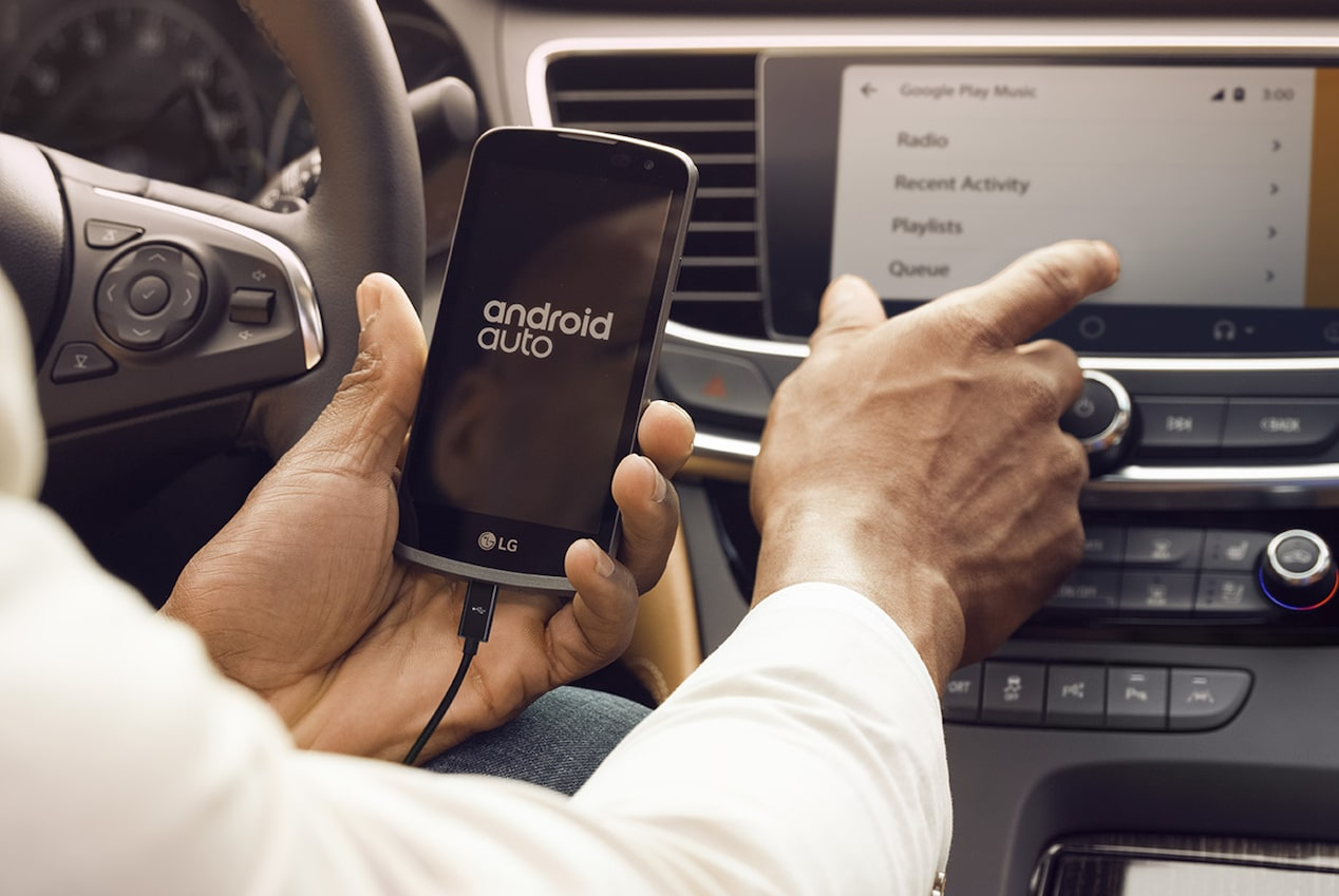 Image showing a man using his smartphone to access the Android Auto pairing feature in the 2018 Buick LaCrosse full-size luxury sedan.