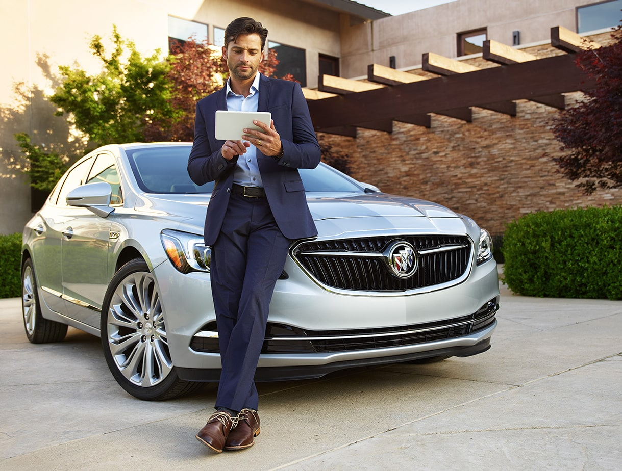 Image of a man using the 4G LTE Wi-Fi Hotspot while leaning on the hood of the 2018 Buick LaCrosse full-size luxury sedan.