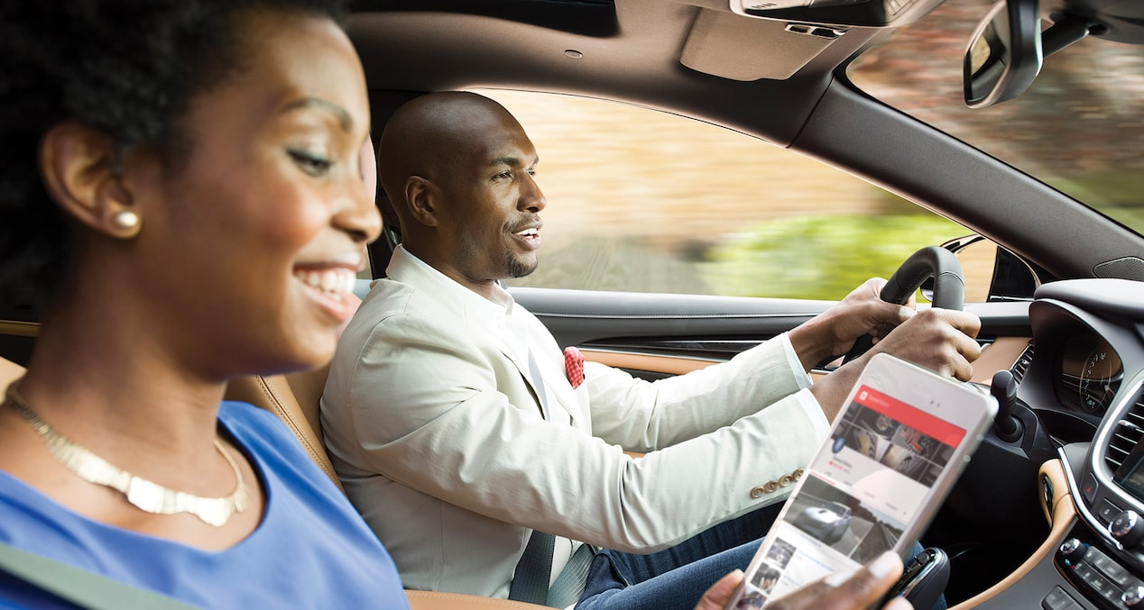 Image of a woman enjoying the available OnStar 4G LTE Wi-Fi hotspot in the 2018 Buick LaCrosse full-size luxury sedan.