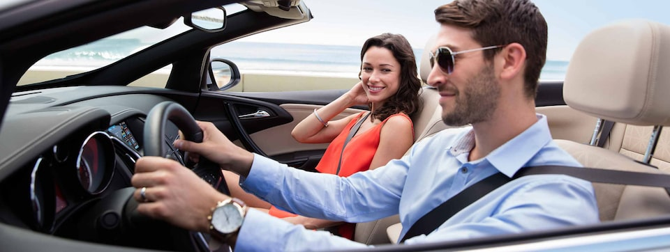 Image of a man and woman enjoying a drive in the 2018 Buick Cascada luxury convertible.
