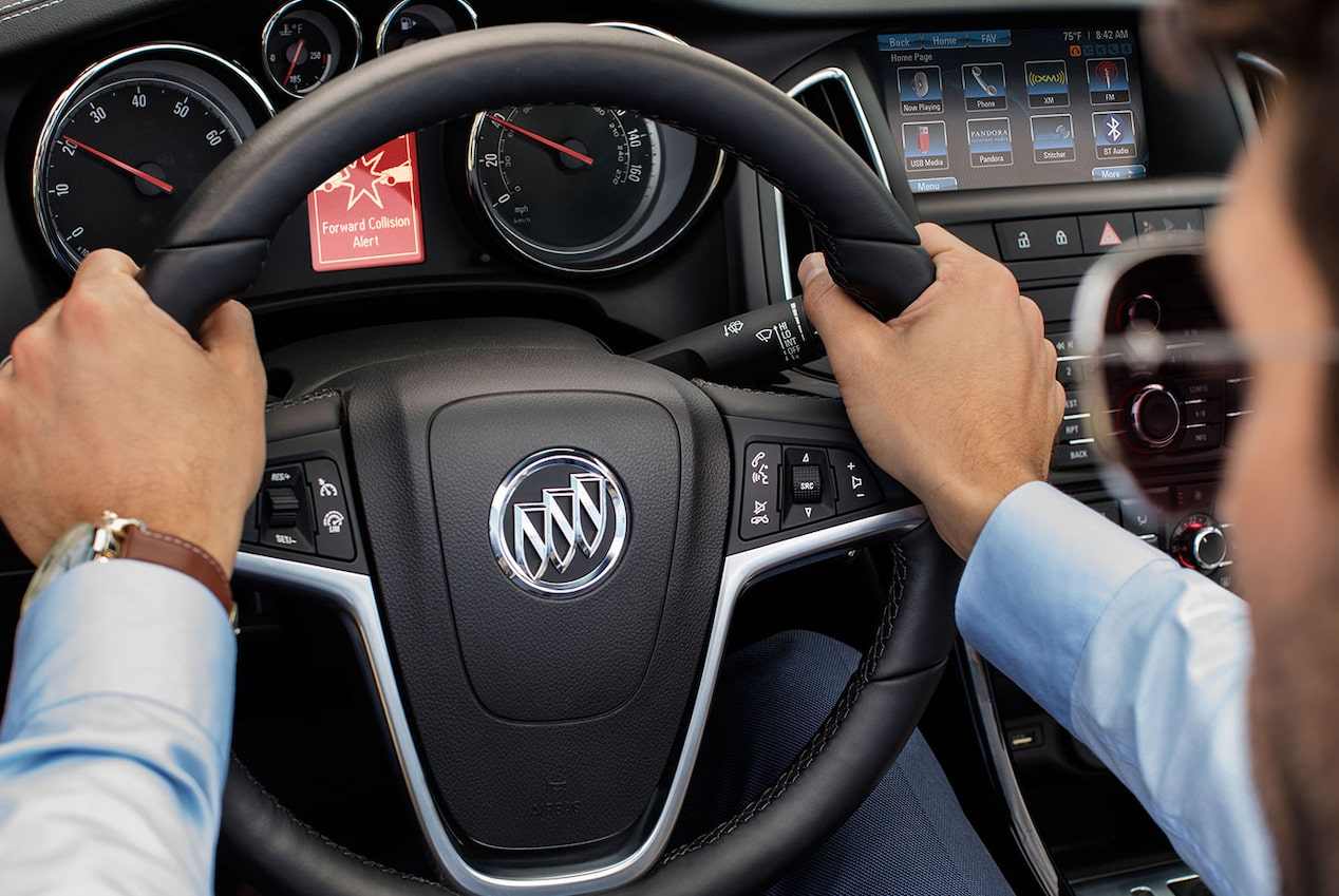Image of a man holding the steering wheel featuring the brand insignia in the 2018 Buick Cascada luxury convertible.