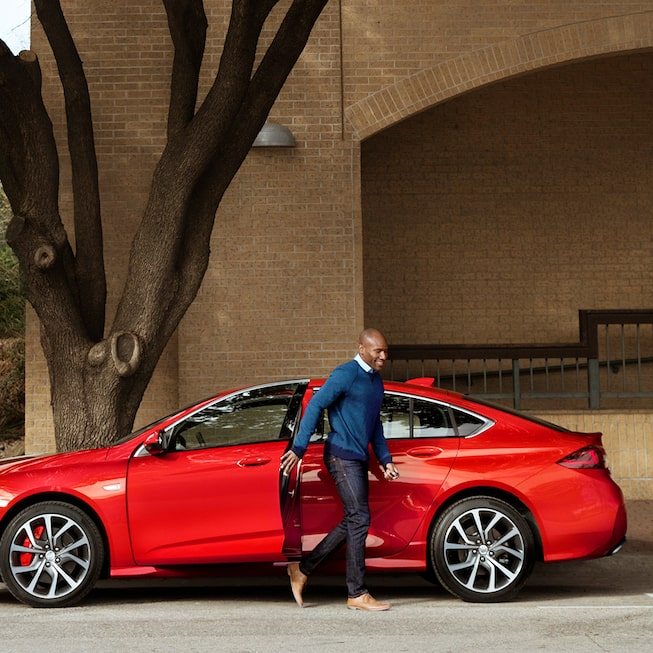 A man going out of the 2020 Buick Regal GS Mid-Size Luxury Sedan profile view
