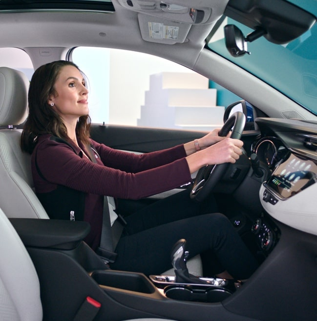 Woman in drivers seat of a 2020 Buick Encore Small Luxury SUV