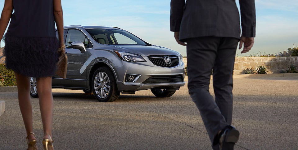 Two People Walking Toward The 2020 Buick Envision Compact SUV